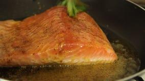 Mujer que cocina los pescados de color salmón en casa almacen de metraje de vídeo