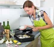Mujer que cocina pescados con la salsa Imagen de archivo