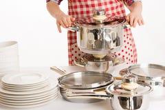Mujer que cocina, sosteniendo los utensilios de la cocina y el pote Imagenes de archivo