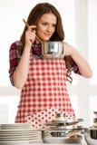 Mujer que cocina, sosteniendo los utensilios de la cocina y el pote Foto de archivo libre de regalías