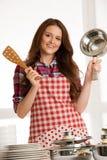 Mujer que cocina, sosteniendo los utensilios de la cocina y el pote Imagen de archivo