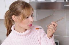Mujer que cocina una comida sabrosa imagenes de archivo