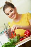 Mujer que cocina verduras Fotos de archivo