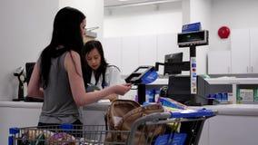 Mujer que coge su medicina de la prescripción y que paga la tarjeta de crédito almacen de metraje de vídeo