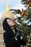 Mujer que coloca el árbol de navidad cercano Foto de archivo