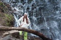 Mujer que coloca la cascada cercana de la montaña Imágenes de archivo libres de regalías
