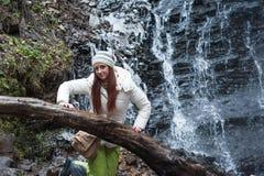 Mujer que coloca la cascada cercana de la montaña Fotos de archivo