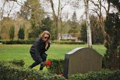 Mujer que coloca las flores en la lápida mortuaria en cementerio Foto de archivo