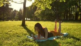 Mujer que coloca sobre hierba verde mientras que mecanografía un mensaje en el teléfono almacen de metraje de vídeo
