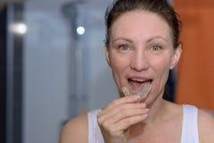 Mujer que coloca una placa de la mordedura en su boca imagen de archivo libre de regalías