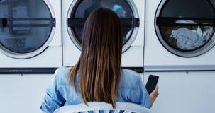 Mujer que come café mientras que usa el teléfono móvil en la lavandería 4k metrajes