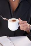 Mujer que come café con leche Foto de archivo