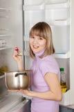 Mujer que come de la cacerola cerca del refrigerador Imagenes de archivo