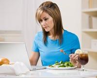 Mujer que come el almuerzo sano mientras que pulsa en la computadora portátil Imágenes de archivo libres de regalías