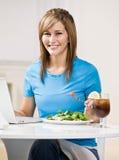 Mujer que come el almuerzo sano mientras que pulsa en la computadora portátil Fotografía de archivo