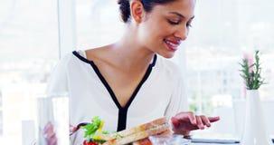 Mujer que come el almuerzo y que usa la tableta almacen de video