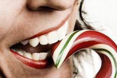 Mujer que come el bastón de caramelo Imagenes de archivo