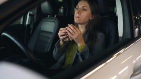 Mujer que come el bocadillo que se sienta en el coche en el aparcamiento Concepto de una vida ocupada moderna almacen de video