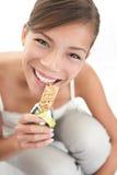 Mujer que come el bocado de barra del muesli Imágenes de archivo libres de regalías