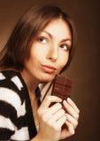 Mujer que come el chocolate Imagenes de archivo