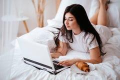 Mujer que come el cruas?n y que trabaja en el ordenador port?til imagen de archivo libre de regalías