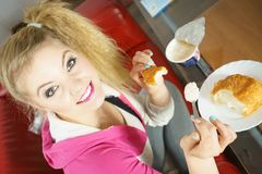 Mujer que come el cruasán y el yogur Fotografía de archivo