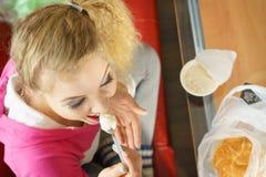 Mujer que come el cruasán y el yogur Fotografía de archivo libre de regalías