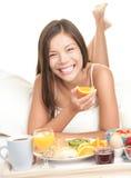 Mujer que come el desayuno en cama Imagen de archivo libre de regalías