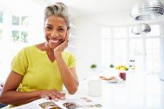 Mujer que come el desayuno y que lee la revista Imagen de archivo libre de regalías