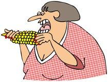 Mujer que come el maíz en la mazorca Fotos de archivo