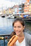 Mujer que come el perrito caliente danés tradicional de los alimentos de preparación rápida Fotografía de archivo