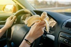 Mujer que come el plátano mientras que conduce en la carretera Fotografía de archivo