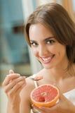 Mujer que come el pomelo imagenes de archivo