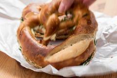 Mujer que come el pretzel alem?n de Brezel con las cebolletas y la mantequilla foto de archivo libre de regalías