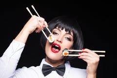 Mujer que come el sushi por dos palillos Fotos de archivo