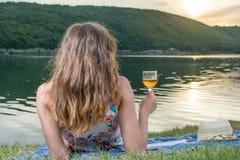 Mujer que come el vidrio de vino por el lago Fotos de archivo