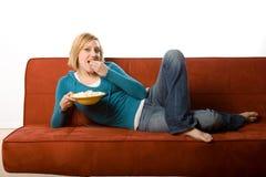 Mujer que come en el sofá Imagen de archivo libre de regalías