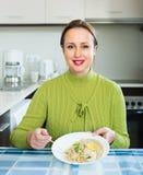 Mujer que come en la cocina Fotografía de archivo libre de regalías