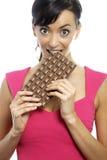 Mujer que come la barra de chocolate Fotografía de archivo