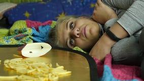 Mujer que come la comida basura con el gran disfrute la muchacha come las patatas fritas Cámara lenta metrajes