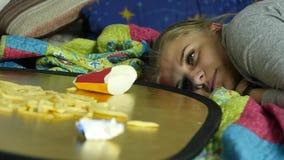 Mujer que come la comida basura con el gran disfrute la muchacha come las patatas fritas Cámara lenta almacen de metraje de vídeo