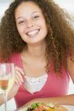 Mujer que come la comida, mealtime con un vidrio de vino Imágenes de archivo libres de regalías