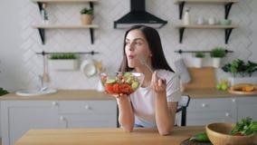 Mujer que come la ensalada en cocina almacen de metraje de vídeo