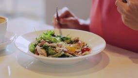 Mujer que come la ensalada para el almuerzo en el restaurante almacen de video