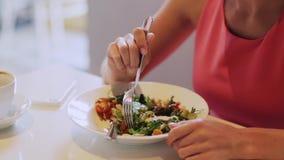Mujer que come la ensalada para el almuerzo en el restaurante almacen de metraje de vídeo