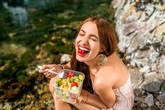 Mujer que come la ensalada sana cerca del río Imágenes de archivo libres de regalías