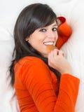 Mujer que come la galleta en cama Fotos de archivo libres de regalías