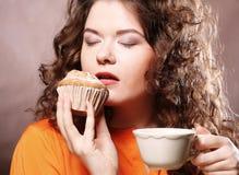Mujer que come la galleta y que bebe el café. Fotografía de archivo libre de regalías