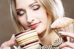 Mujer que come la galleta y que bebe el café. Imágenes de archivo libres de regalías