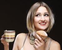 Mujer que come la galleta y que bebe el café. Imagenes de archivo